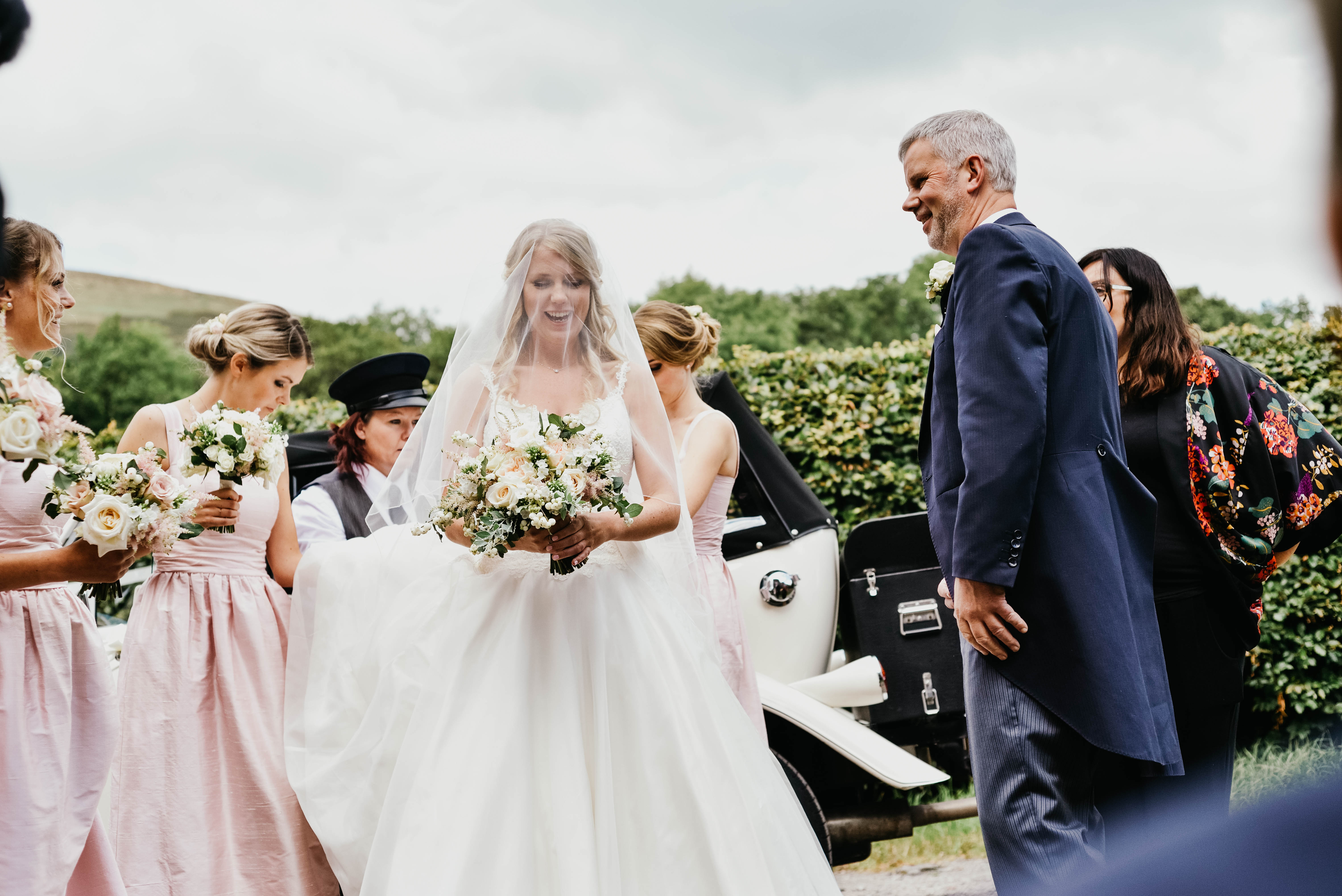 A bride smiles as her bridesmaids straighten her dress