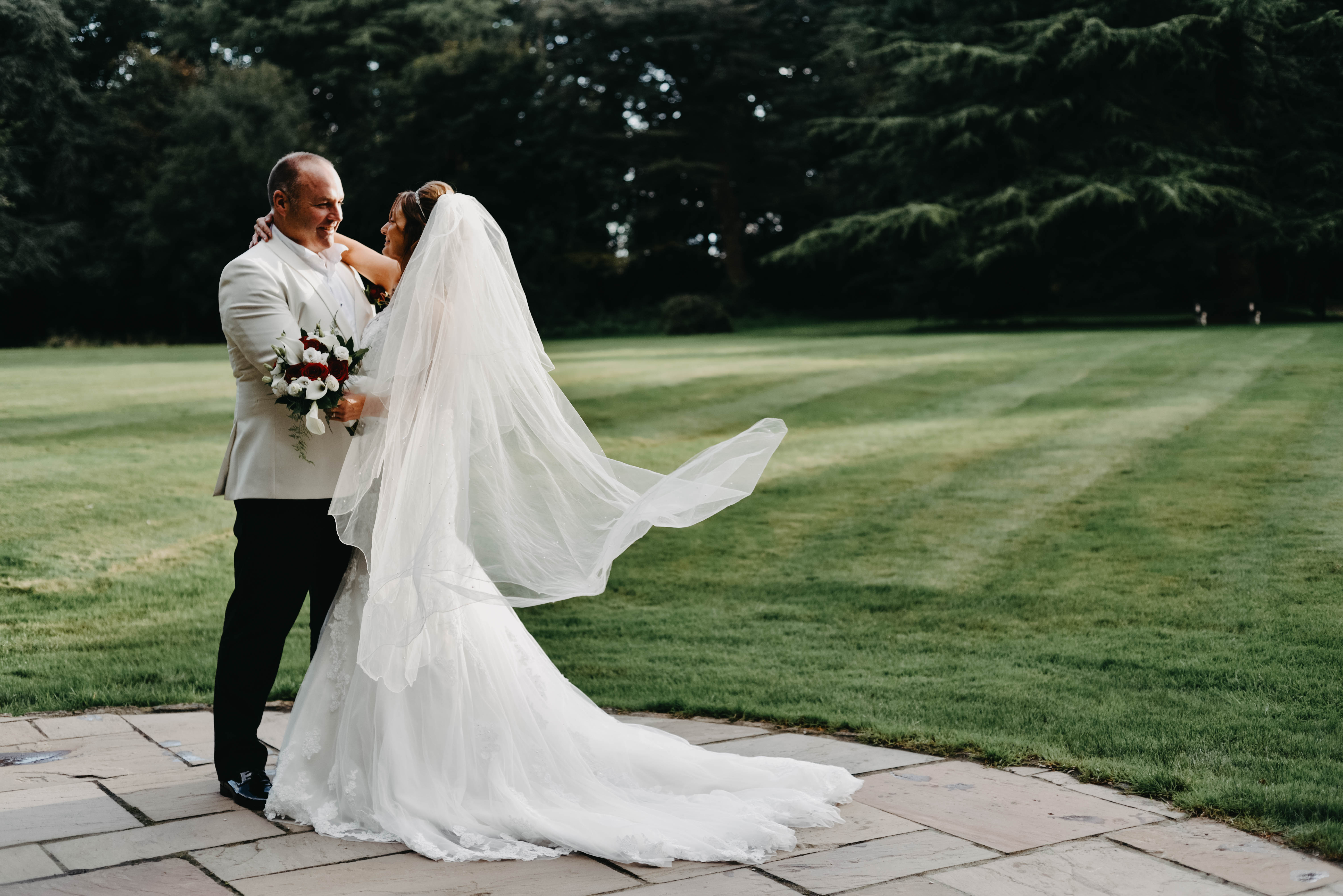 bride and groom standing on a lawn