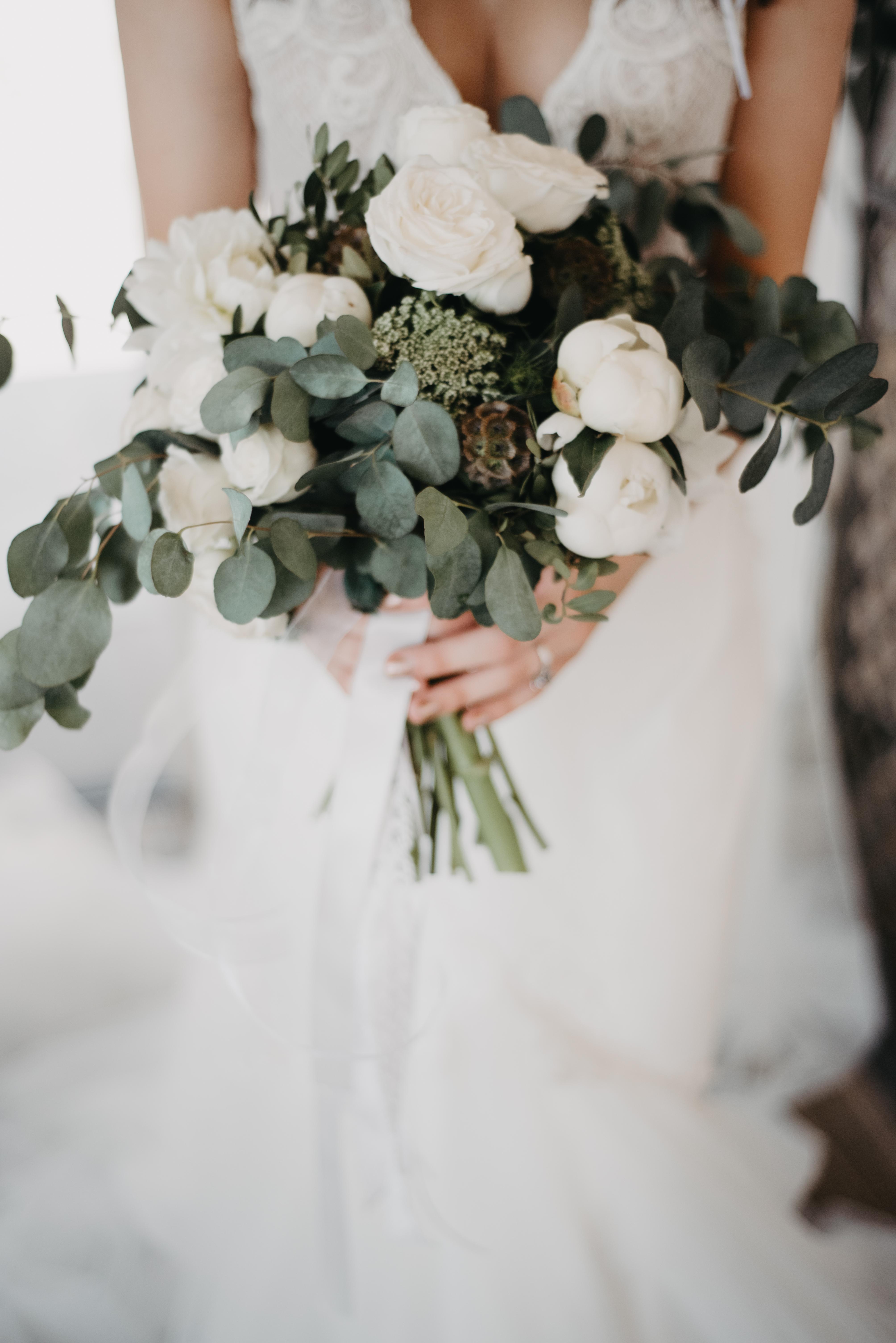 bride holding a bunch of eucalyptus