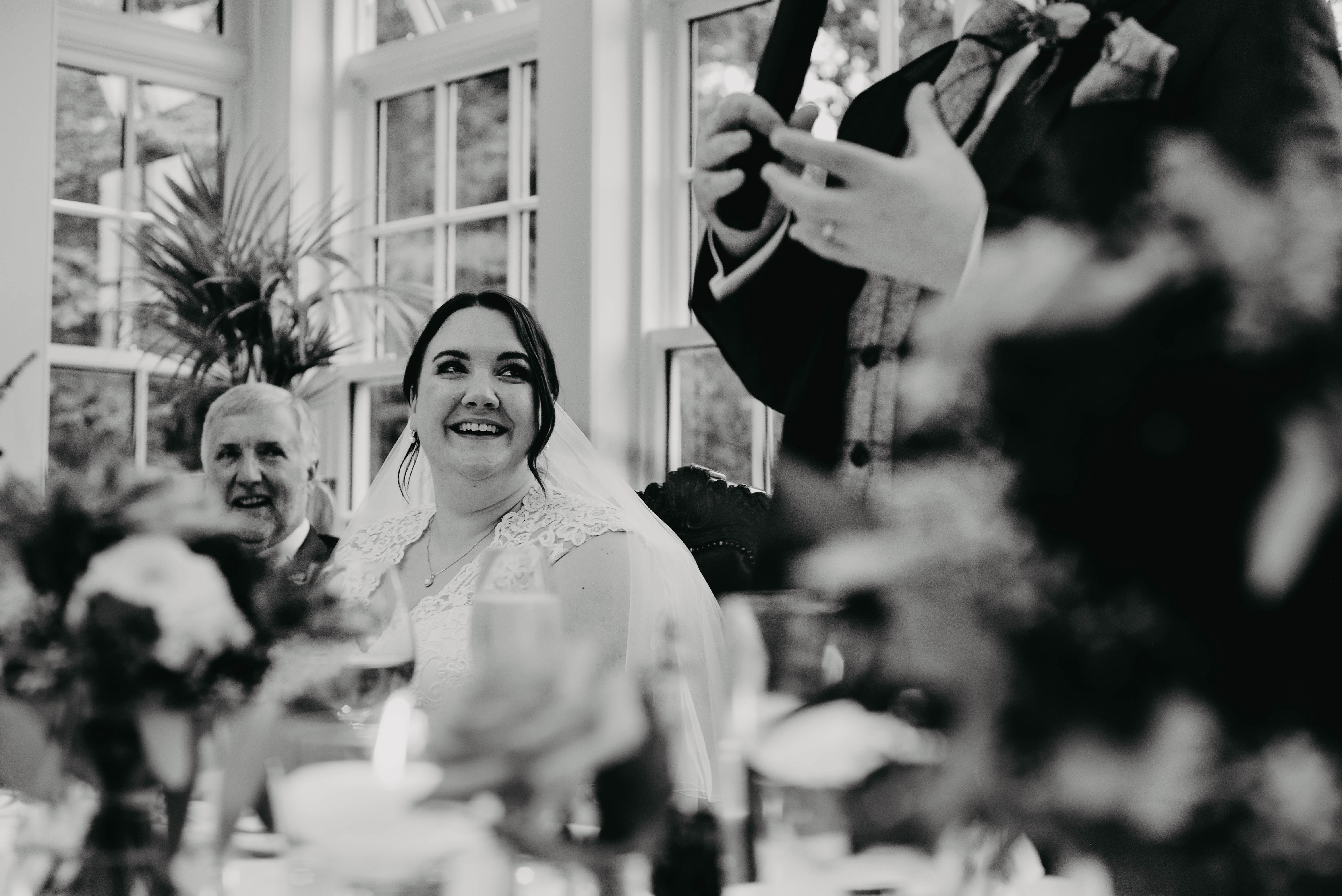 bride smiles during the grooms speech