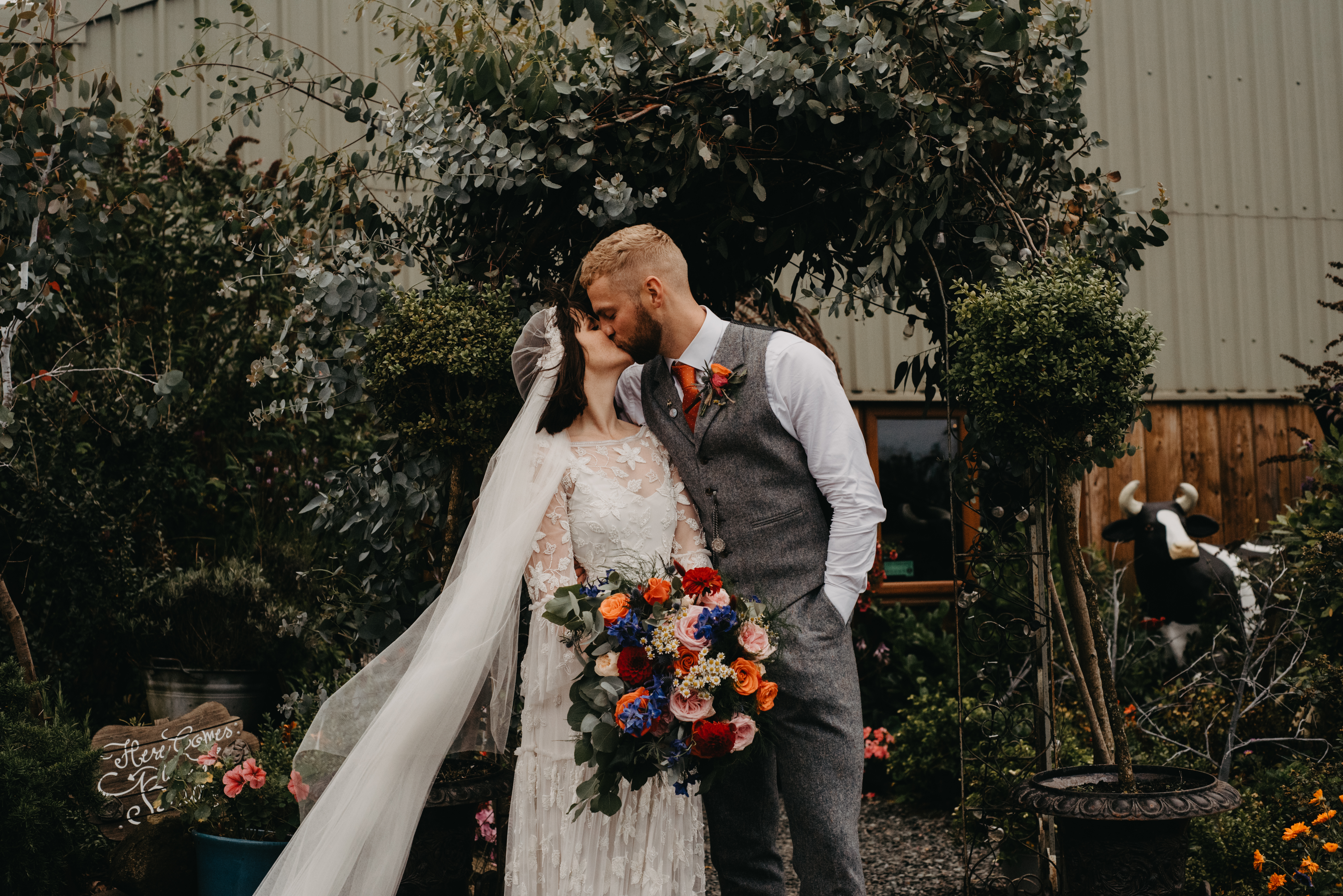 A bride and groom kiss at the entrance of their wedding reception