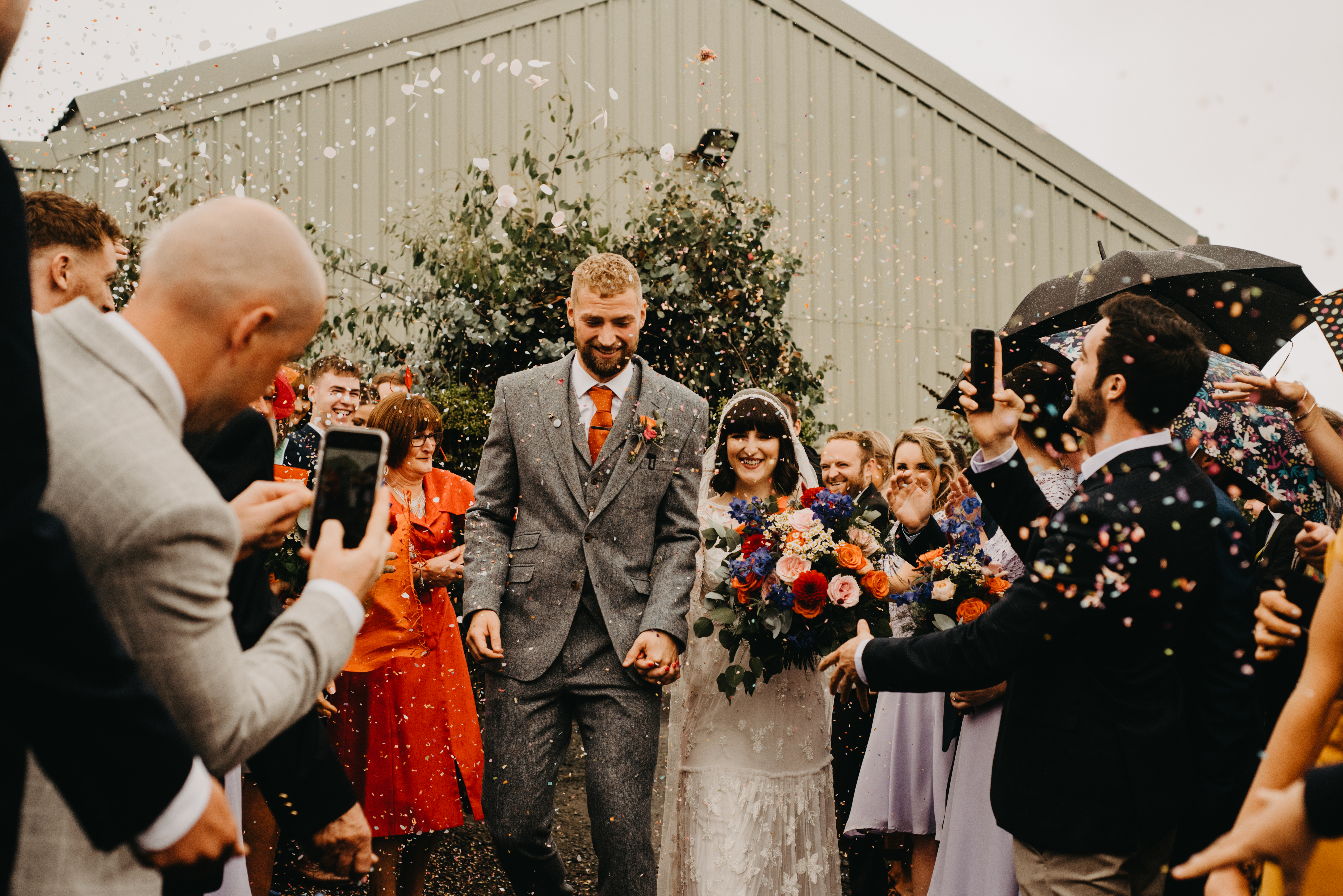 Bride and groom walks while guests throws confetti over them