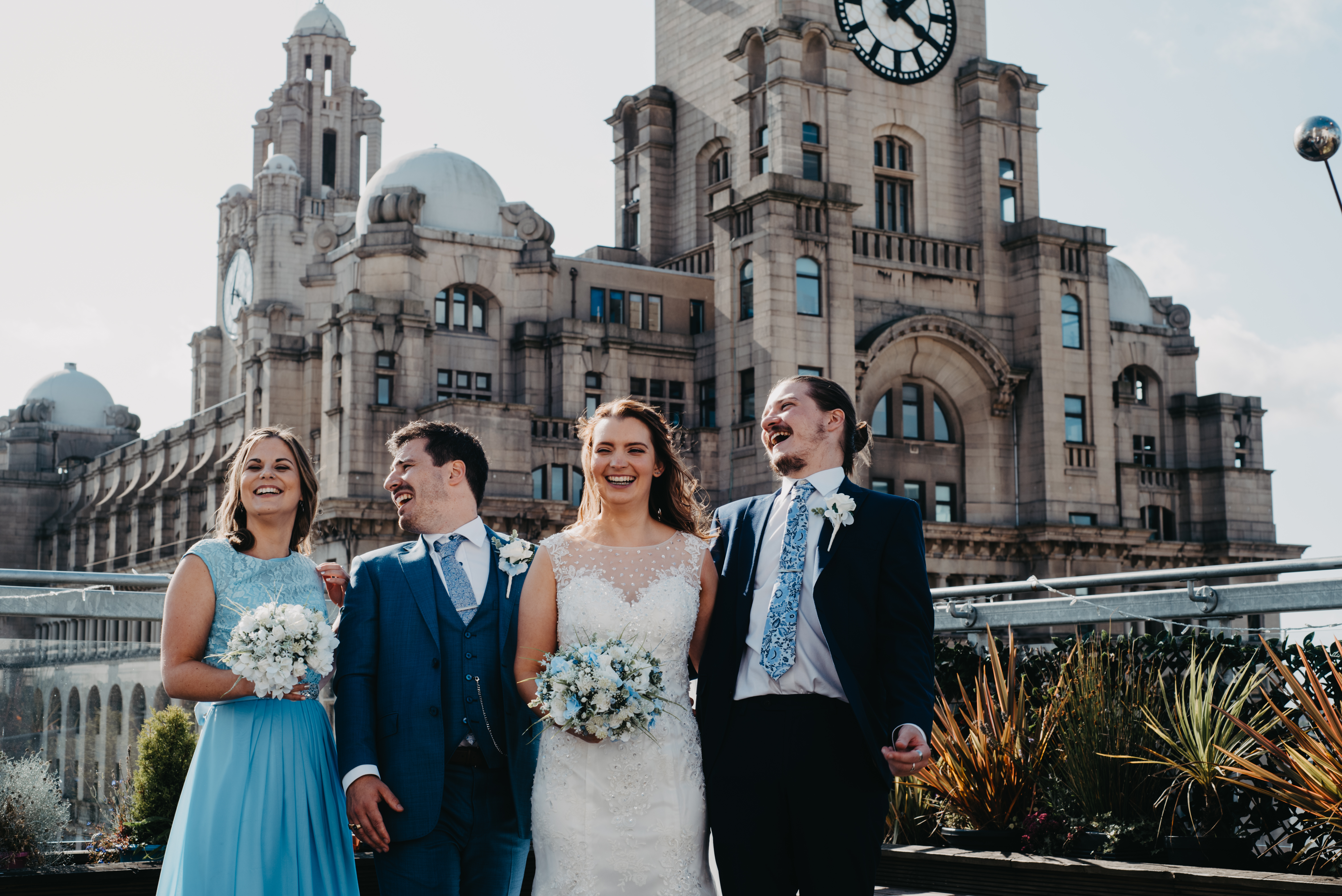 Bride and groom laughing with their siblings